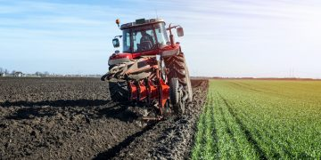 Tractor agricultural machine cultivating field.