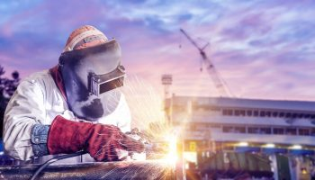 double exposure concept, worker arc welder piping welding buiding in shipyard background soft monotone