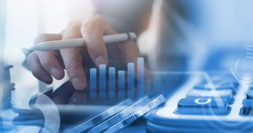 Business analysis, accounting and finance investment concept. Double exposure of business man working on digital tablet and coins with digital diagram, business data, financial graph